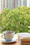 Tazza di tè caldo con la pila di libri sulla tavola di legno dalla finestra, con fondo vago Fotografie Stock Libere da Diritti