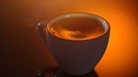 Tazza di tè caldo con vapore su fondo brillante video d archivio