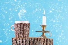 Tazza di tè caldo in sciarpa della lana e della candela in combustione del bastone della candela sul ceppo di legno fotografia stock