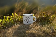 Tazza di tè caldo su fondo della natura durante il tramonto Vacanze attive di avventura di concetto all'aperto Campeggio estivo immagini stock libere da diritti