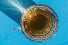 tazza di tè caldo sui precedenti blu, vista superiore Immagine Stock