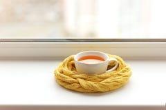 Tazza di tè caldo in una sciarpa su un davanzale della finestra ad una finestra fotografie stock libere da diritti