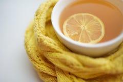 Tazza di tè caldo in una sciarpa su un davanzale della finestra ad una finestra Immagine Stock