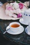 Tazza di tè che sta la ciotola vicina di zucchero e della teiera Fotografie Stock