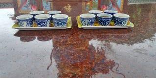 Tazza di tè cinese del drago blu e riflessione del drago sull'altare di marmo rosso Immagini Stock Libere da Diritti