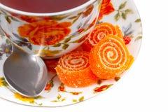 Tazza di tè classica con i fiori rossi ed arancioni Immagini Stock