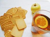 tazza di tè con i biscotti del limone e di una mela che si trova su un fondo bianco Fotografia Stock