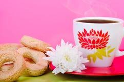 Tazza di tè con i biscotti e un fiore adorabile fotografie stock