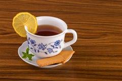 Tazza di tè con i biscotti, il limone e la menta Immagini Stock Libere da Diritti