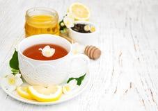 Tazza di tè con i fiori del gelsomino Immagine Stock
