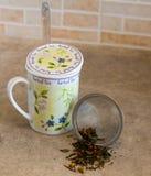 Tazza di tè con il cucchiaio ed il filtro Immagine Stock