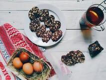 tazza di tè con il limone, budino al cioccolato, uova, dolce sulla tavola Fotografia Stock