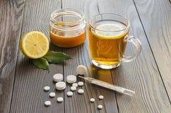 Tazza di tè con il limone e hovey, pillole e termometro Fotografie Stock Libere da Diritti