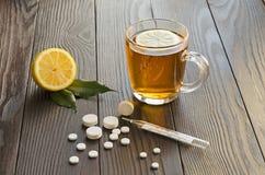 Tazza di tè con il limone, le pillole ed il termometro Fotografia Stock