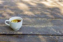 Tazza di tè con il limone su fondo di legno al parco immagini stock libere da diritti