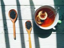 tazza di tè con il limone, tè all'ingrosso su un cucchiaio di legno su un fondo bianco Immagine Stock Libera da Diritti