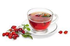 Tazza di tè con la rosa selvatica isolata su fondo bianco Immagine Stock