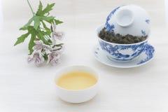 Tazza di tè con le foglie di tè ed i fiori Fotografia Stock Libera da Diritti