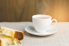 Tazza di tè con pane per la prima colazione su fondo di legno Immagini Stock