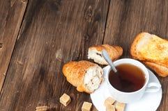 Tazza di tè con un croissant e un pane tostato su una vecchia tavola di legno blu Fotografia Stock
