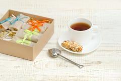 Tazza di tè, delle barre di muesli e del filtro del tè Scatola con le barre W bianco Immagine Stock Libera da Diritti