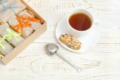 Tazza di tè, delle barre di muesli e del filtro del tè Scatola con le barre W bianco Fotografie Stock