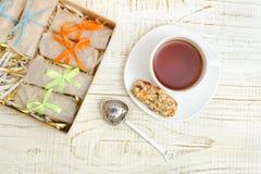 Tazza di tè, delle barre di muesli e del filtro del tè Scatola con le barre W bianco Fotografia Stock