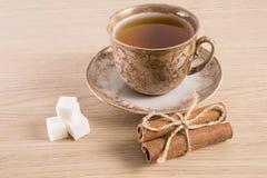 Tazza di tè di Brown e piattino, un pacco dello zucchero della cannella su fondo di legno leggero Immagini Stock