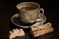 Tazza di tè di Brown e piattino, un pacco di cannella, zucchero Fotografia Stock