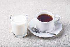 Tazza di tè e bicchiere di latte su un fondo leggero Fotografia Stock