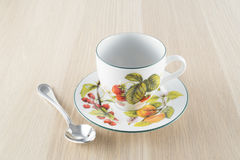 Tazza di tè e cucchiaino sulla tavola di legno immagine stock
