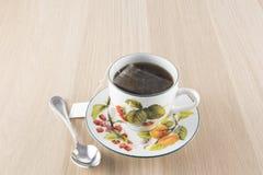 Tazza di tè e cucchiaino sulla tavola di legno fotografia stock