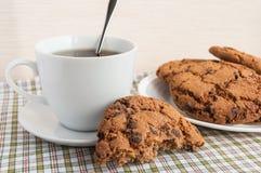Tazza di tè e dei biscotti con cioccolato Americano fotografie stock libere da diritti