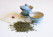 Tazza di tè e delle foglie di tè con la busta Immagini Stock Libere da Diritti