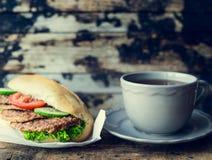 Tazza di tè e di un panino con carne su un fondo di legno scuro, tonificata fotografia stock