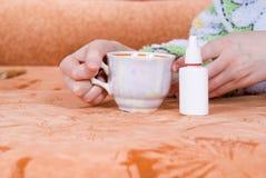 Tazza di tè e di uno spruzzo nasale Fotografia Stock Libera da Diritti