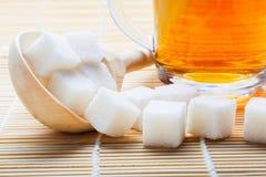 Tazza di tè e di zucchero in un cucchiaio di legno sulla stuoia Fotografia Stock Libera da Diritti