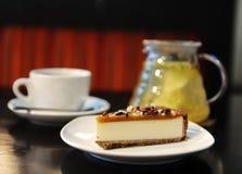 Tazza di tè e dolce su una tavola in caffè Fotografie Stock Libere da Diritti