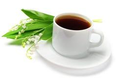 Tazza di tè e gigli della valle Immagini Stock