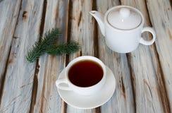 Tazza di tè e una teiera su una tavola fotografie stock