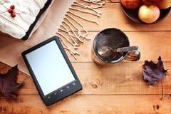 Tazza di tè, il libro elettronico, foglie di acero di autunno su un fondo di legno Immagini Stock Libere da Diritti