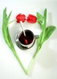 Tazza di tè nel cuore dei tulipani Immagine Stock