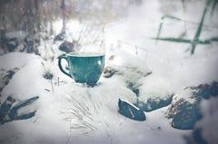 Tazza di tè nella bufera di neve di inverno Immagine Stock