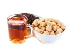Tazza di tè nero, ciotola con il tè asciutto, zucchero bruno Immagine Stock Libera da Diritti