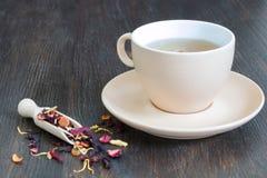 Tazza di tè nero con i petali e le erbe Immagine Stock Libera da Diritti