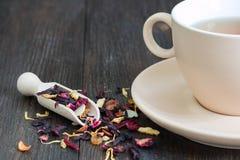 Tazza di tè nero con i petali e le erbe Fotografia Stock Libera da Diritti