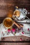 Tazza di tè nero con la canna da zucchero, rose, foglie di tè su un fondo di legno marrone Fotografia Stock