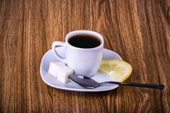 Tazza di tè nero con zucchero ed il limone Fotografia Stock