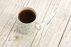 Tazza di tè nero su un fondo di legno Immagine Stock Libera da Diritti