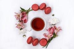 Tazza di tè nero in un cerchio di Alstroemeria dei fiori e dei biscotti di mandorla su fondo bianco Fotografie Stock Libere da Diritti
